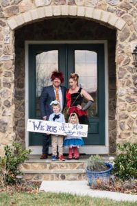 Robert Betters and family in Halloween costumes posing on a doorstep